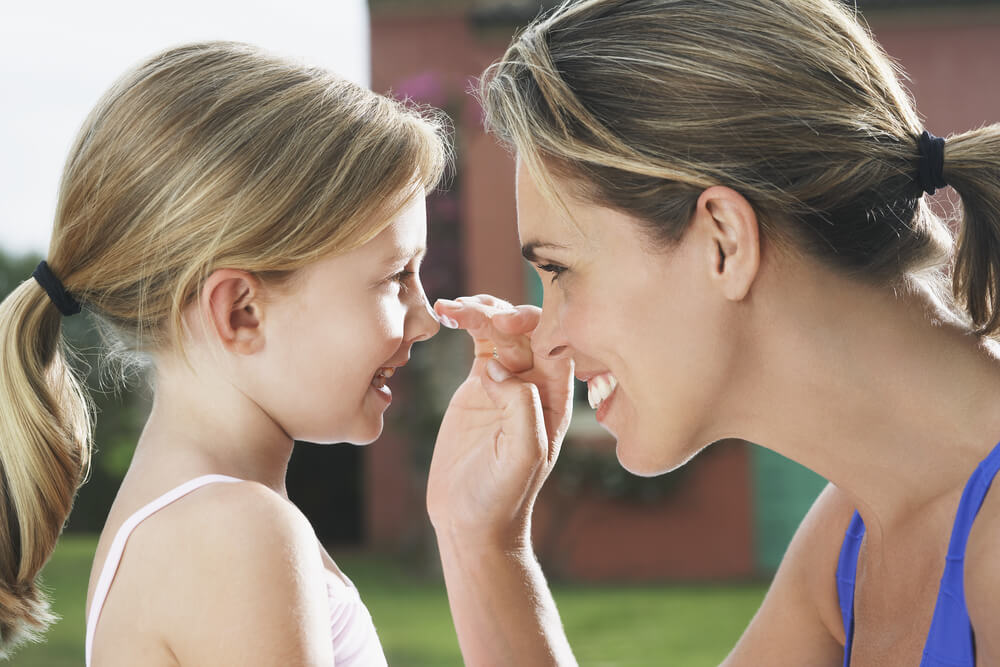 Smiling mom applying sunscreen to small girl's nose.