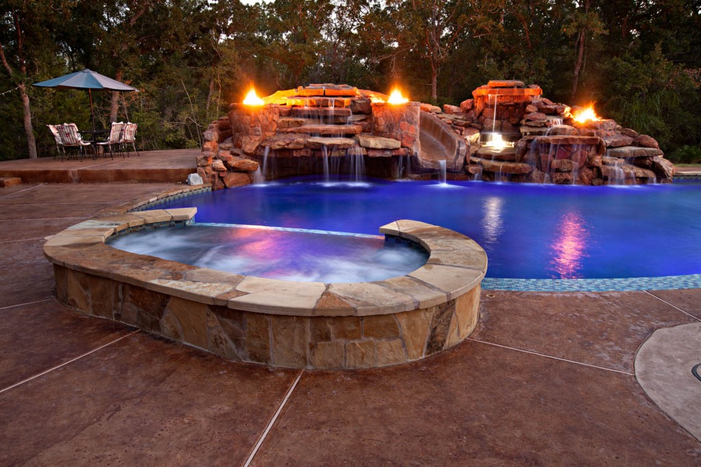 Stamped and stained concrete decking surrounding a spa and pool with large waterfall grotto and exotic fire features.
